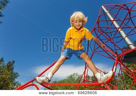 Smiling boy stands on red rope with legs apart