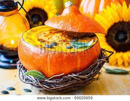 Cream of pumpkin soup with pumpkin seeds and sage  in pumpkin.Selective focus
