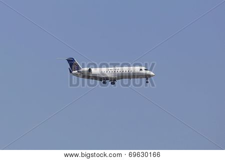 United Express Canadair CRJ-100 jet in New York sky before landing at JFK Airport