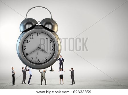 Big old-style clock and many businesspeople around