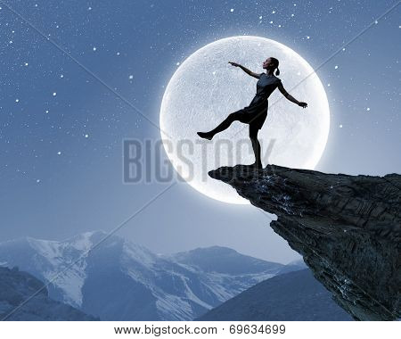 Silhouette of woman walking on edge of rock