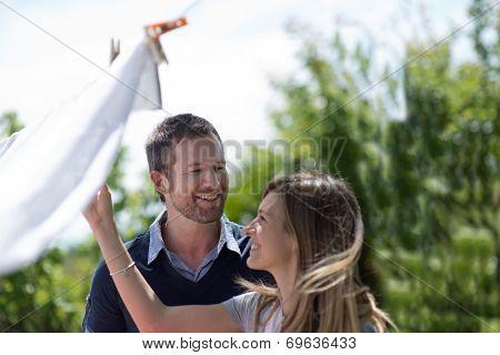 Happy couple hanging up laundry