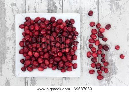 Cranberry fruit over weathered wooden white background.