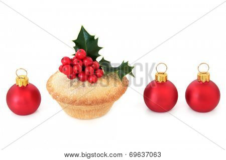 Christmas mince pie cake with red bauble decorations and holly over white background.
