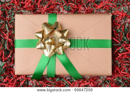 High angle shot of a plain wrapped brown paper Christmas present in a field of red and green crepe paper. The package has green ribbon and a gold bow.