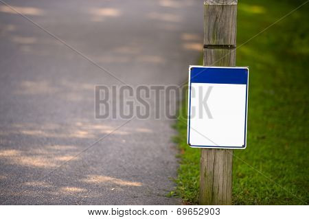 Blank signboard on green grass in park to place your logo or advertising on it