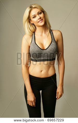 Beautiful shapely curvy young blond woman in sexy sportswear with a bare midriff and sports bra accentuating her full breasts holding her hand to her hair smiling seductively at the camera, on grey
