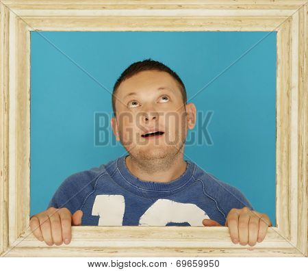 Young Man Inside Wooden Picture Frame Thinking of Something.