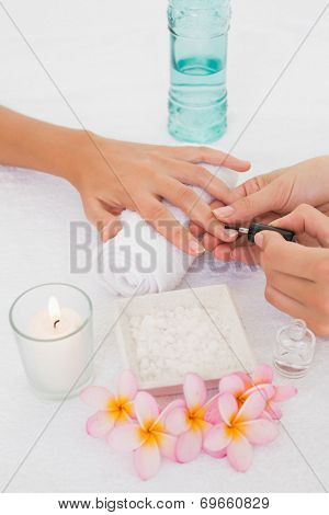 Close up of beautician applying nail varnish to female client's nails at spa beauty salon