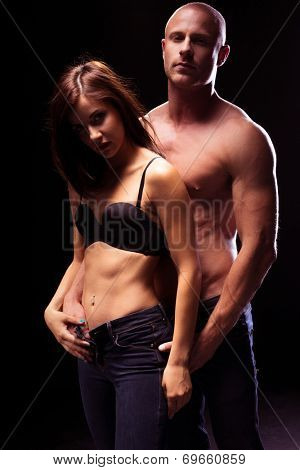 Very Sexy Couple Seductively Flaunting Flat Abs, Isolated on Black Background. Posing for Fashion photo.