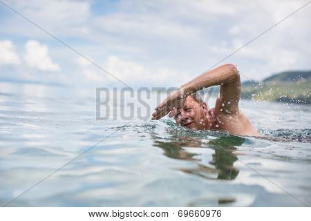 Senior man swimming in the Sea/Ocean - enjoying active retirement, having fun, taking care of himself, staying fit