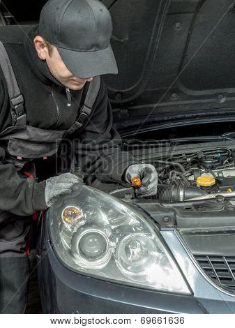 Auto mechanic replacing winker bulb in passenger car