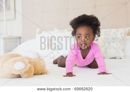 Baby girl in pink babygro crawling on bed at home in the bedroom