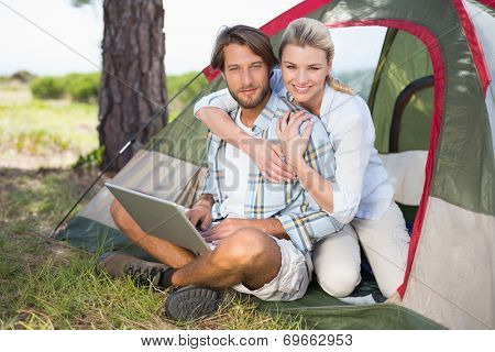 Attractive couple sitting by their tent using laptop smiling at camera on a sunny day