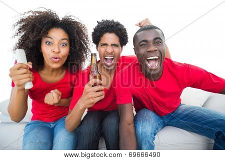Football fans in red cheering on the sofa with beers on white background