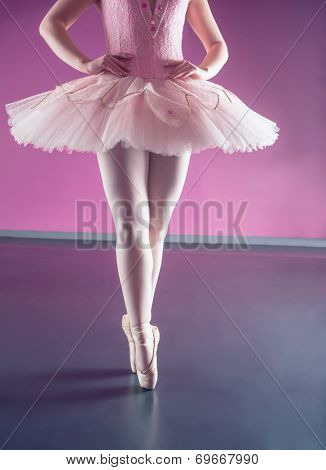 Graceful ballerina standing en pointe in the ballet studio