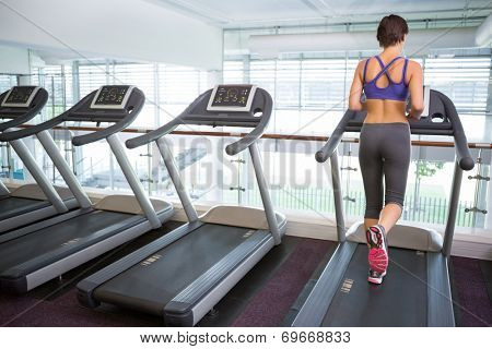 Fit brunette running on the treadmill at the gym