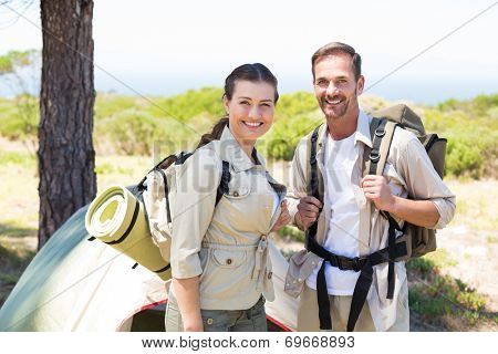 Outdoorsy couple smiling at camera outside their tent on a sunny day
