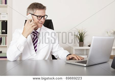 Medical Doctor Using Mobile Phone And Laptop