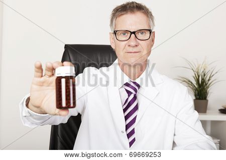 Pharmacist Holding Out A Bottle Of Pills