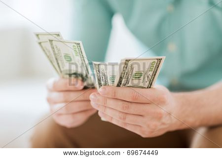 savings, finances, economy and home concept - close up of man counting money at home
