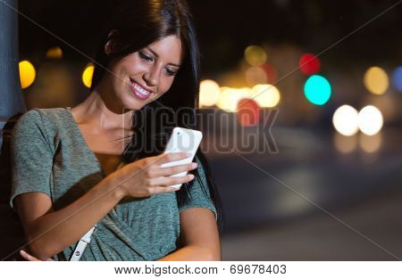 Beautiful Woman Use Her Phone In The City At Night.