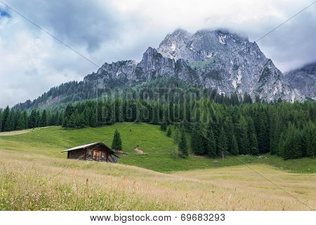 Wooden House In A Green Meadow Near Mountains