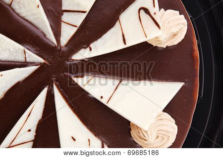 chocolate cream brownie cake topped with white chocolate slice and cream flowers on black plate isolated over white background