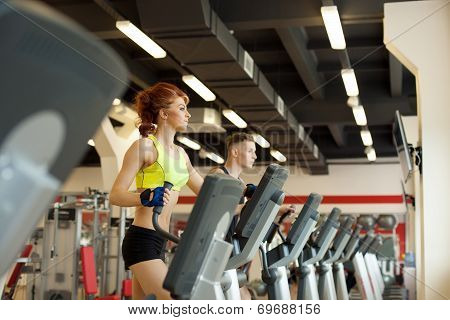 Lovely girl posing on treadmill in gym