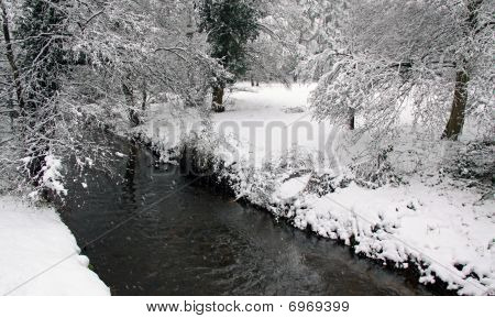 A river flowing through forest in winter snow