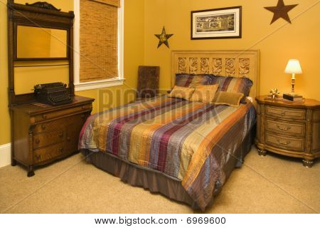 Bed With Striped Bedspread In Affluent Home