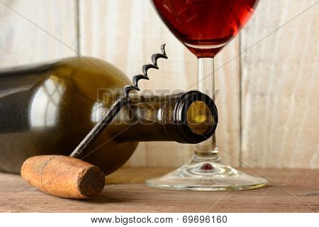 Wine still life with a bottle on its side and the bottom of a glass of red wine and a cork screw leaning on the bottle.  Horizontal format with shallow depth of field on a wood background.