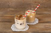 stock photo of ice-cubes  - Iced coffee with milky ice cubes and cold milk with coffee ice cubes in glasses on wooden background - JPG