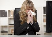 stock photo of influenza  - Young businesswoman blowing her nose as she sits at her desk at work suffering from seasonal hayfever a cold or influenza - JPG