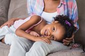 picture of lap  - Cute daughter lying across mothers lap at home in the living room - JPG
