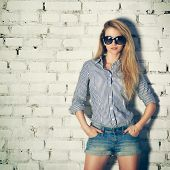 stock photo of toned  - Portrait of Young Hipster Woman with Hands in Pockets on White Brick Wall Background - JPG