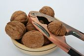 picture of cleaving  - Walnuts in wooden bowl and a nutcracker - JPG