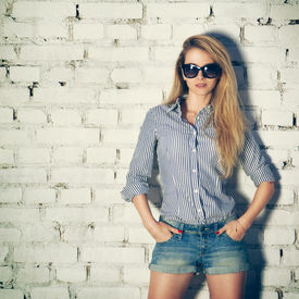 pic of independent woman  - Portrait of Young Hipster Woman with Hands in Pockets on White Brick Wall Background - JPG