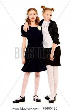Portrait of two ten years schoolgirls wearing uniform. Isolated over white.