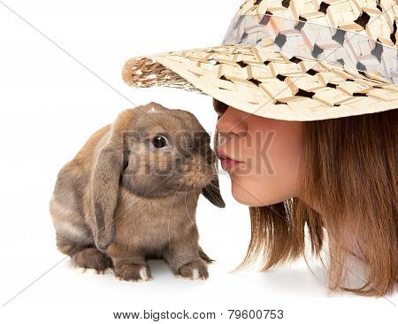 Girl in a straw hat kisses dwarf rabbit.