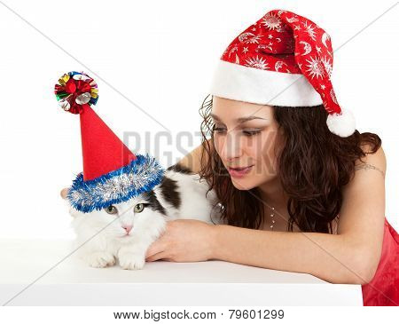 Beautiful girl with a cat in New Year's caps.