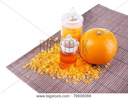 Bottles of essential oil and bath salt near orange on bamboo mat isolated on white