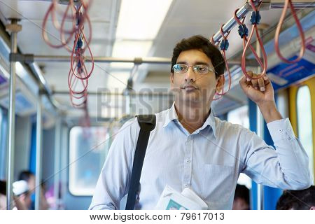 Asian Indian businessman taking ride to work, standing inside train.