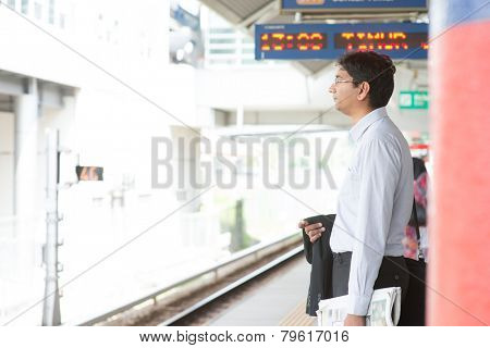 Candid Asian Indian businessman waiting at public train station.