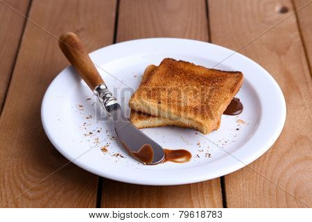 Toast bread with chocolate on plate with knife on wooden table background