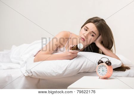 beauty lying on the bed with a clock and pills