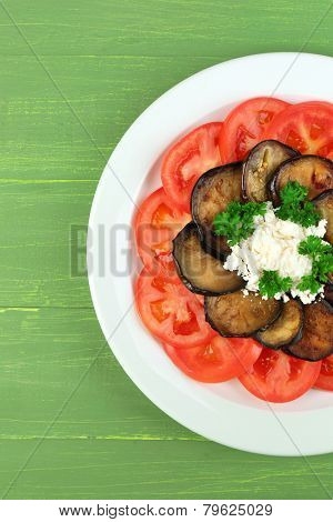 Eggplant salad with tomatoes and feta cheese, on wooden background