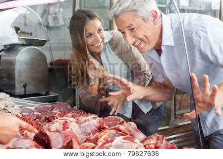 Happy couple buying fresh meat at butcher's shop