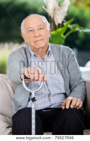 Portrait of elderly man holding metal cane while sitting on couch at nursing home porch