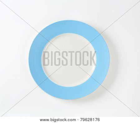 white plate with blue rim on white background
